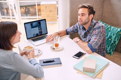 Man and woman conducting a business meeting in local cafe royalty free stock images