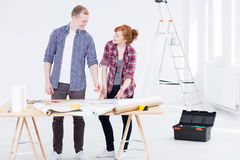 Man and the woman consulting the project. Man and the women standing together close to the drafting board and consulting the project with the ladder and tool box Royalty Free Stock Photos