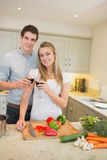 Man and woman cooking and clinking wine glasses Stock Photos