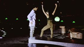 A man and a woman cool dance at night in the side light. stock video