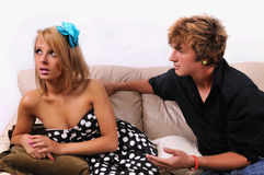 Man and woman on couch. Man coming on to a seemingly uninterested woman on a couch Stock Images