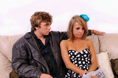 Man and woman on couch. Man sitting next to a seemingly uninterested or angry woman on a couch Stock Images