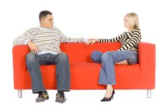Man And Woman On Couch With Serious Expressions. Man and woman sitting on separate ends of a couch with serious expressions, facing each other.  Hands are Royalty Free Stock Image