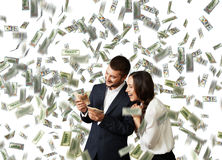 Man and woman counting money. Excited laughing businessman and businesswoman standing under dollar's rain and counting money Royalty Free Stock Image