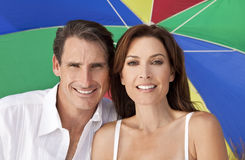 Man & Woman Couple Colorful Umbrella on Beach. Man and woman romantic couple under a colorful sun umbrella or parasol on a beach Royalty Free Stock Photo