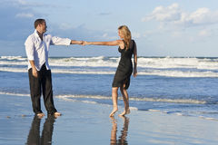 Man and Woman Couple Having Fun Dancing On A Beach. A young man and woman holding hands and having fun dancing as a romantic couple on a beach with a bright blue Stock Photos