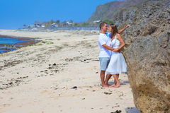 MAN & WOMAN COUPLE HOLDING HANDS KISSING ON BEACH Stock Images