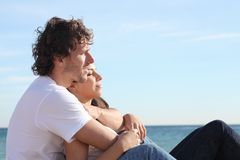 Man and woman couple hugging on the beach and flirting. Man and women couple hugging on the beach and flirting under the sunlight stock image