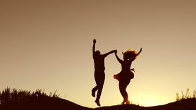 Man and woman couple in love silhouette jumping in slow motion video. Man and woman joy running sunlight and jumping on