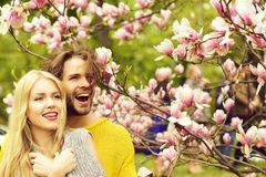 Man and woman, couple in love in spring magnolia flowers stock photo