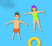 Man and woman, couple relaxing floating, swimming on a back in beach pool Stock Photography
