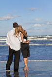 Man and Woman Couple In Romantic Embrace On Beach. A young man and woman embracing as a romantic couple on a beach with a bright blue sky Royalty Free Stock Photography