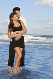 Man and Woman Couple In Romantic Embrace On Beach. A young man and woman embracing as a romantic couple on a beach with a bright blue sky Stock Image