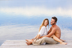 Man and woman couple sitting on a jetty at a seaside. Side view of a men and women couple sitting on a jetty at a seaside Royalty Free Stock Photos