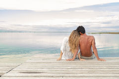 Man and woman couple sitting on a Jetty under a blue cloudy sky Royalty Free Stock Images