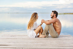 Man and woman couple sitting on a jetty under a blue cloudy sky Royalty Free Stock Photo