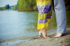 Man and woman couple standing on the beach near the water Stock Photography