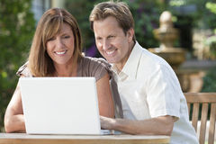 Man & Woman Couple Using Laptop Computer In Garden. Attractive, successful and happy middle aged men and women couple in their thirties, sitting together outside Stock Photos