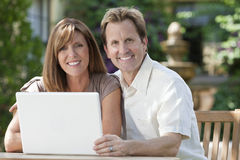 Man & Woman Couple Using Laptop Computer In Garden Stock Image