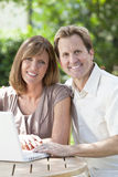 Man & Woman Couple Using Laptop Computer In Garden. Attractive, successful and happy middle aged men and women couple in their thirties, sitting together outside Royalty Free Stock Photography