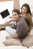 Man & Woman Couple Using Laptop Computer At Home. Happy man and woman couple in their thirties, sitting together at home on a sofa using a laptop computer Royalty Free Stock Photo