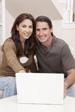 Man & Woman Couple Using Laptop Computer At Home. Happy man and woman couple in their thirties, sitting together at home on a sofa using a laptop computer Stock Photo