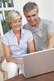 Man & Woman Couple Using Laptop Computer At Home. Happy men and women couple in their forties, sitting together at home on a sofa using a laptop computer Royalty Free Stock Photo