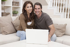 Man & Woman Couple Using Laptop Computer At Home. Happy men and women couple in their thirties, sitting together at home on a sofa using a laptop computer Royalty Free Stock Images