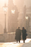 Man and woman couple walk on Charles Bridge in foggy morning, Prague, Czech Republic. Romantic Prague theme Royalty Free Stock Image