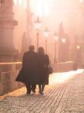 Man and woman couple walk on Charles Bridge in foggy morning, Prague, Czech Republic. Romantic Prague theme Royalty Free Stock Photo