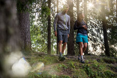 Man and woman couple walking in forest woods with sun flare light. Group of friends people summer adventure journey in. Man and women couple walking in forest Royalty Free Stock Images