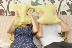 Man and woman covering their faces with pillows. Man and women covering their faces with pillows in the living room Royalty Free Stock Photos