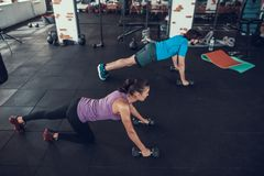 Man And Woman Crawling In Gym With Dumbbells. Man And Woman Crawling With Dumbbells. Training Day. Fitness Club. Healthy Lifestyle. Powerful Athlete. Active stock photos