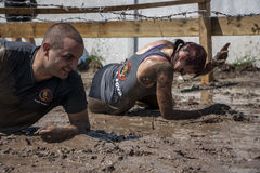 A man and a woman crawling under barbed wire. During the strength race Legion Run held in Sofia, Bulgaria on 26 July 2014 royalty free stock photos