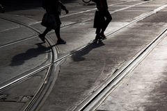 Man and woman crossing the street. Silhouette of Man and woman crossing a street with rails on the asphalt stock photography