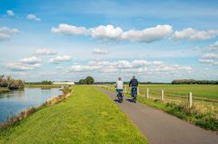 Man and woman cycle on a bike path at the top of a. Two unidentified people cycle on a cycle path at the top of a along a narrow river at the Dutch National Park royalty free stock photo