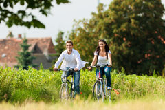 Man and woman cycling in summer Stock Photo