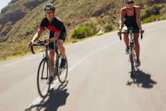 Man and woman cyclist riding down the country road Royalty Free Stock Photography