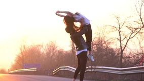 A pair of ballet dancers on the road dance, a man performs support in the air