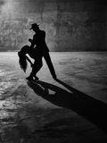 Man and woman dancing, concrete building surroundings Stock Photos