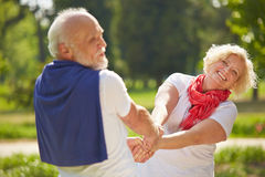 Man and woman dancing together in a garden stock photos