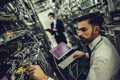 Man and woman in data centre. Handsome men and attractive women are working in data centre. IT engineer specialists in network server room. Running diagnostics stock images