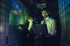 Man and woman in data centre. Handsome men and attractive women are working in data centre with laptop. IT engineer specialists in network server room. Running Royalty Free Stock Image