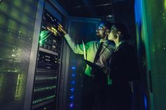 Man and woman in data centre. Handsome men and attractive women are working in data centre with laptop. IT engineer specialists in network server room. Running Royalty Free Stock Photos