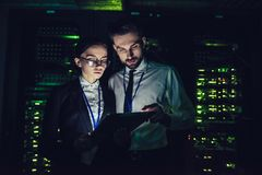 Man and woman in data centre. Handsome men and attractive women are working in data centre with tablet. IT engineer specialists in network server room. Running Stock Images