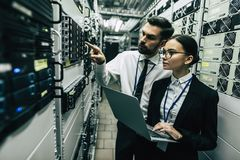 Man and woman in data centre. Handsome men and attractive women are working in data centre with laptop. IT engineer specialists in network server room. Running stock photo