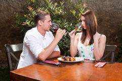 Man and woman on date drinking wine on terrace Royalty Free Stock Image
