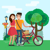 Man and woman on a date in park with flowers and bike. Stock Photos
