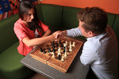 Man and woman deal by playing chess. Man and beautiful women deal by playing chess Royalty Free Stock Images