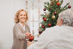 Man and woman decorating christmas tree. Senior men and women decorating christmas tree together Stock Images